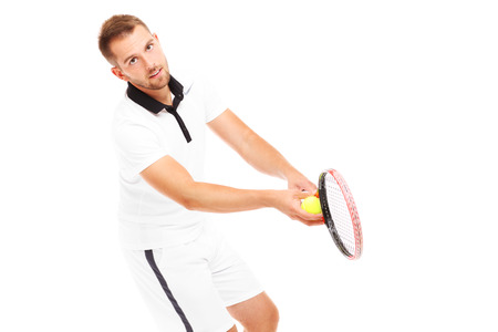 A picture of a handsome tennis player serving a ball over white background photo