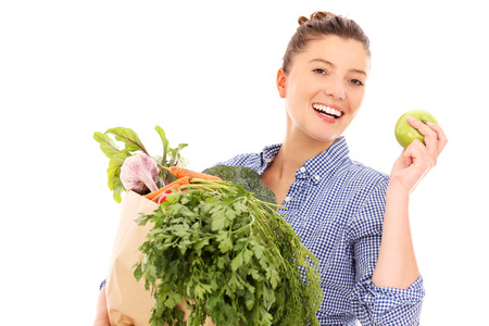 A picture of a happy woman with vegetables and apple over white background photo