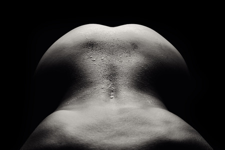 nude female buttocks: A picture of a naked and wet womans back over black background
