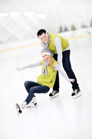 hombre cayendose: Una imagen de una pareja feliz en la pista de hielo