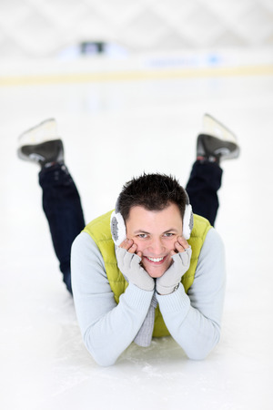iceskates: A picture of a happy man lying on the ice rink