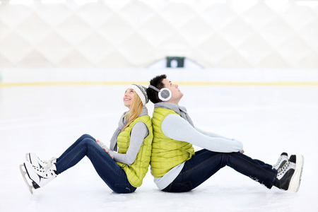 A picture of a happy couple sitting on the skating rink photo