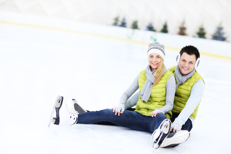 iceskates: A picture of a happy couple sitting on the skating rink Stock Photo