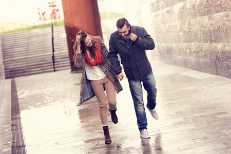 mojada: Una foto de una pareja de jóvenes corriendo en la lluvia en la ciudad
