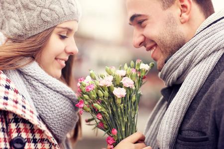 enamorados besandose: Una imagen de un hombre que da las flores a su amante en un día de invierno Foto de archivo