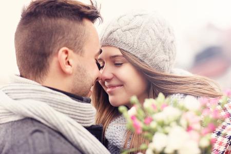 enamorados besandose: Una imagen de una pareja rom�ntica con flores en un paseo de oto�o Foto de archivo