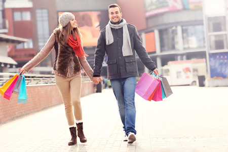 A picture of cheerful young people walking with shopping bags in the city photo