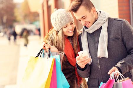comprando: Una imagen de un par de compras con el tel�fono inteligente en la ciudad Foto de archivo