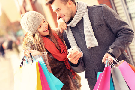 Una imagen de un par de compras con el teléfono inteligente en la ciudad Foto de archivo - 33745370