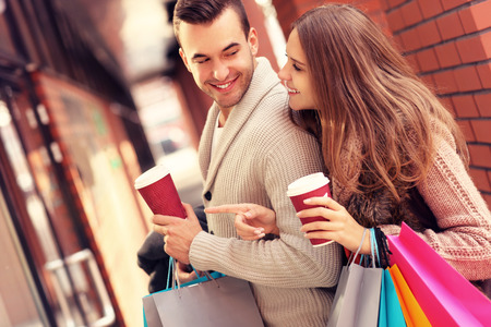 christmas shopping bag: A picture of a joyful couple window shopping in the mall with coffee