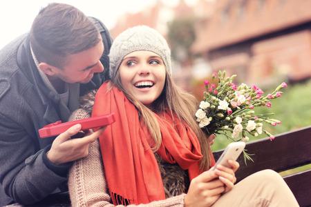 Un ritratto di un uomo che dà regalo a sorpresa alla donna nel parco