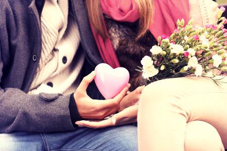 romantik: En midsection av en romantisk par sitter på en bänk i parken håller Valentines gåva och blommor