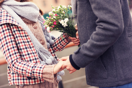 hand holding flower: A midsection of a couple holding hands and flowers