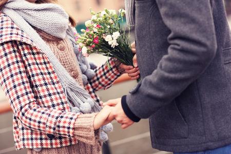 manos entrelazadas: Una sección media de una pareja cogidos de la mano y flores