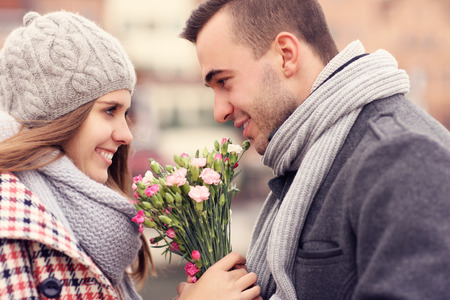 A picture of a romantic couple on a date holding flowers Banco de Imagens