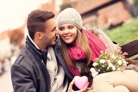 Een foto van een paar op Valentijnsdag in het park met bloemen en hart Stockfoto