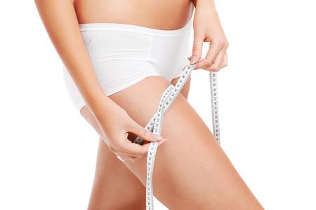 muslos: Una sección media de una mujer del ajuste que mide su muslo sobre el fondo blanco Foto de archivo