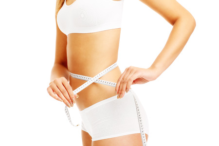 midsection: A midsection of a fit woman measuring her waist over white background