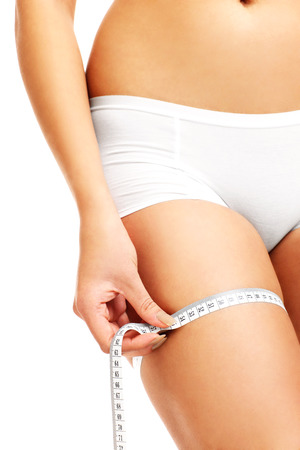 midsection: A midsection of a fit woman measuring her thigh over white background