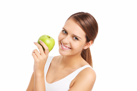 A picture of a happy woman holding a green apple over white background