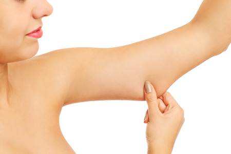 A picture of a frustrated woman showing her imperfect arms over white background