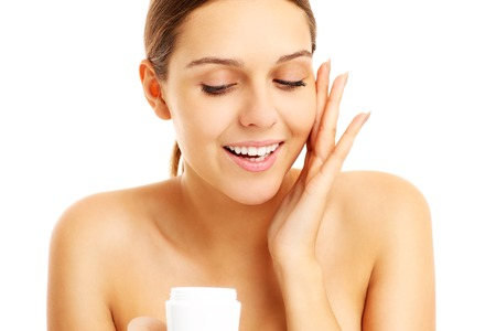 anti wrinkles: A picture of a pretty woman applying cream on face over white background