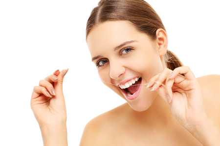 teeth cleaning: A picture of a young woman using dental floss over white background Stock Photo