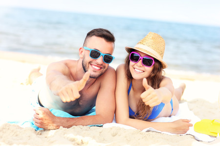 ok: A picture of a happy couple lying on the beach and showing ok signs
