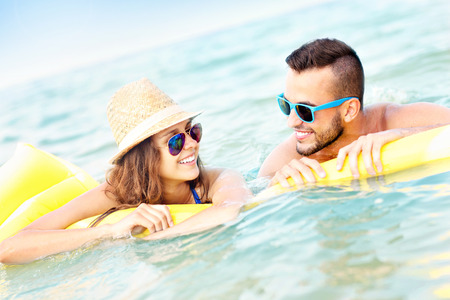 matress: A picture of a young couple having fun on a matress in the sea Stock Photo