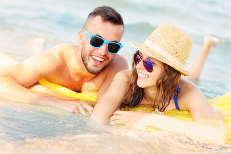 matress: A picture of a young couple swimming on a matress in the sea Stock Photo