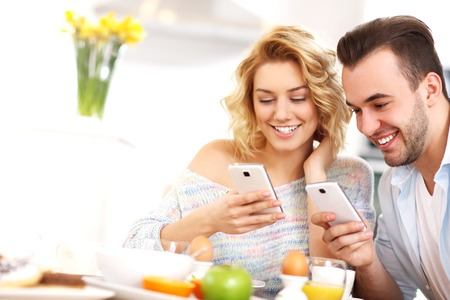 sms message: A picture of a young couple eating breakfast in the kitchen and using smart phone Stock Photo