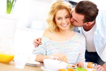 A picture of a young man giving a good morning kiss to his wife in the kitchen
