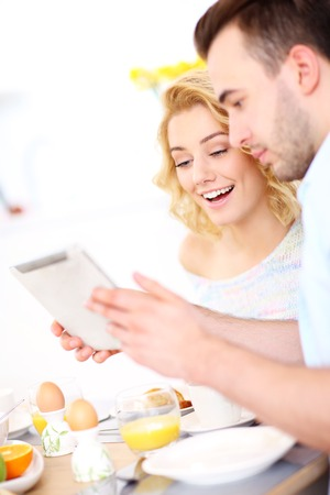 A picture of a young couple eating breakfast in the kitchen and using tablet photo