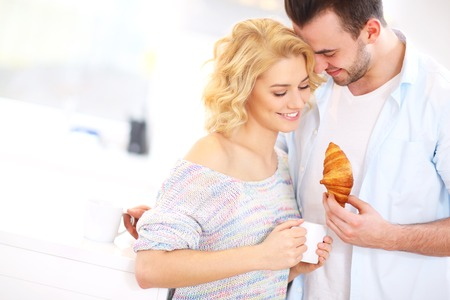 kiss couple: A picture of a young couple eating breakfast and hugginh in the kitchen Stock Photo