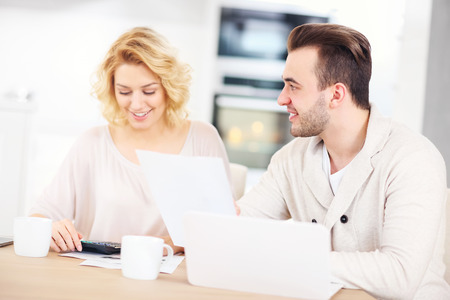family budget: A picture of a happy couple planning home budget in the kitchen Stock Photo