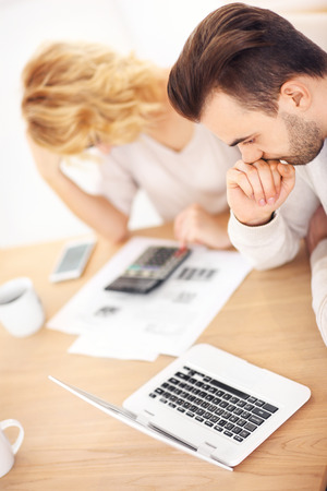 refinance: A picture of a young worried couple with documents at home Stock Photo