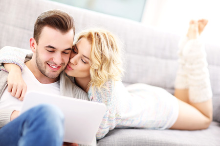 A picture of a romantic couple with laptop in living room photo