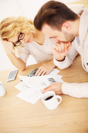refinance: A picture of a worried couple with documents at home
