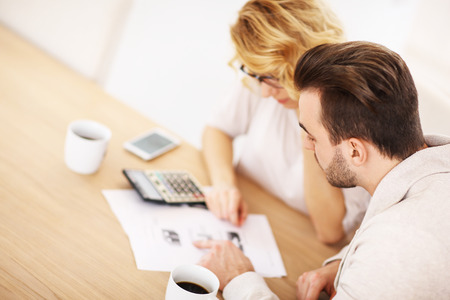 A picture of an adult couple working on documents at home Stock Photo