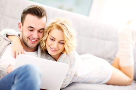 couple on couch: A picture of a romantic couple with laptop in living room