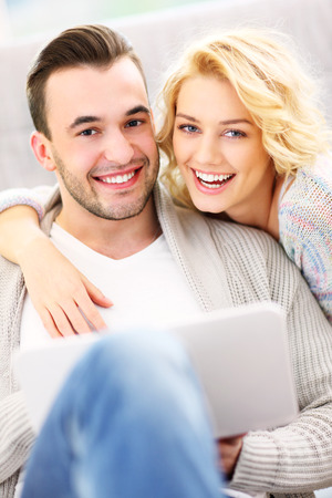 A picture of a happy couple using laptop at home