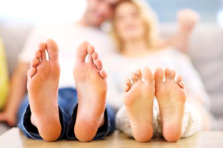 Een foto van barefeet paar liggend op een sofa