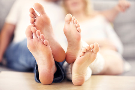 adult foot: A picture of barefeet couple lying on a sofa Stock Photo