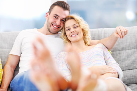 barefoot man: A picture of a young couple relaxing at home