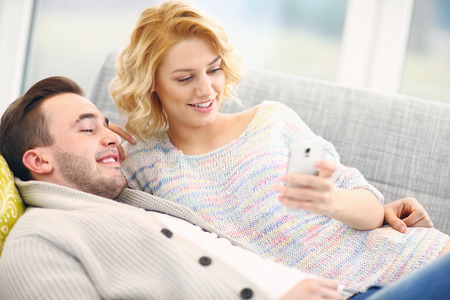 A picture of a young couple relaxing at home and using smart phone photo