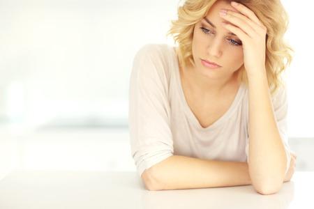 dolor de cabeza: Una foto de una joven mujer deprimida con dolor de cabeza en casa
