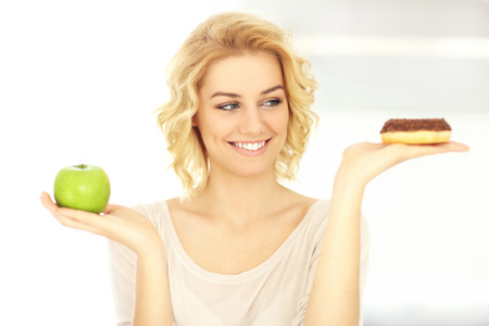 food woman: A picture of a happy woman with donut and apple in the kitchen
