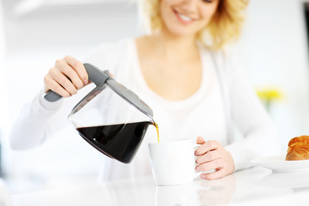 A picture of a young happy woman pouring coffee to a white mug in the kitchen photo
