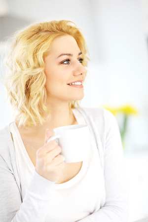 house wife: A picture of a young happy woman drinking coffee in the kitchen Stock Photo