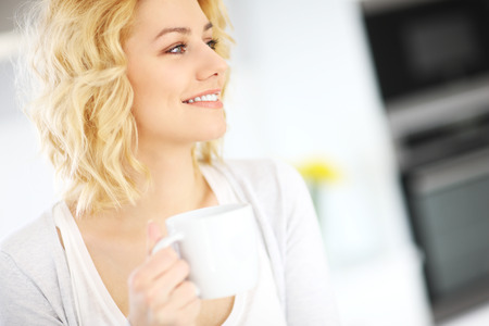 A picture of a young happy woman drinking coffee in the kitchen 版權商用圖片